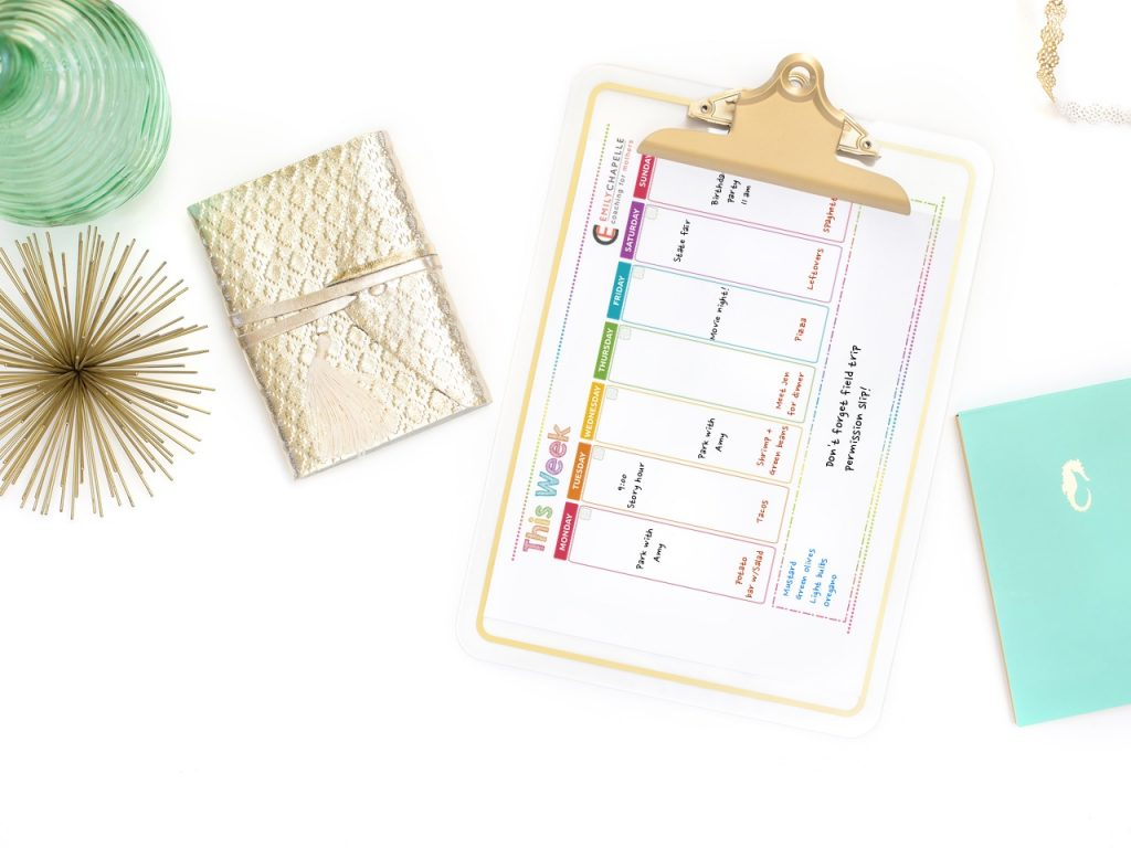 flatlay showing a printable weekly calendar or planner on a clipboard with aqua and gold accessories